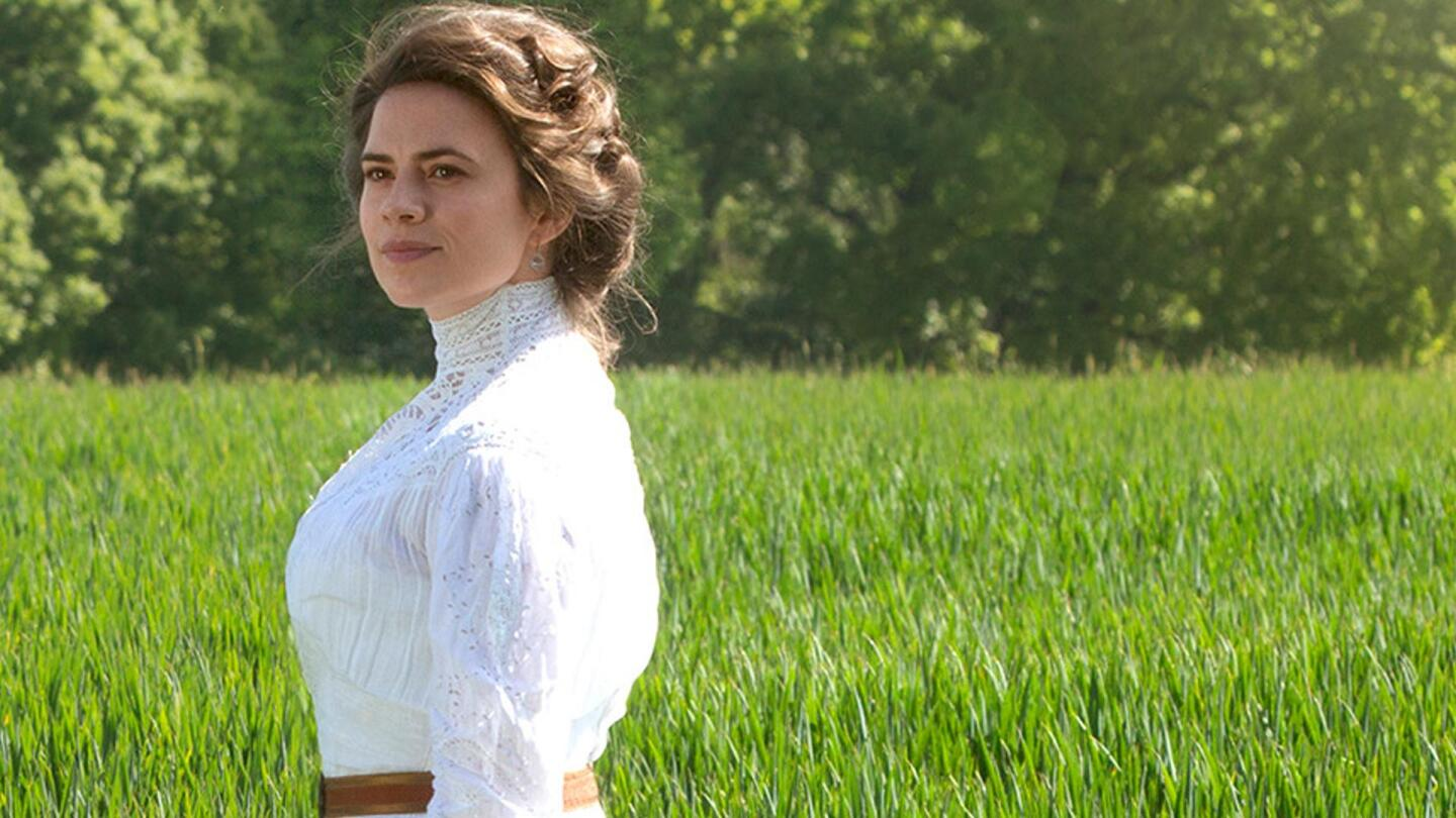 "Margaret Schlegel stands in a verdant green meadow from a scene in Masterpiece's ""Howards End: Episode Four."""