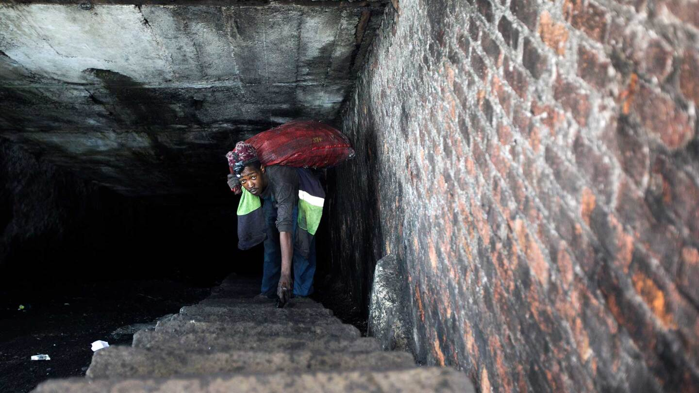 A miner emerges from an abandoned mine in South Africa carrying a heavy sack of coal on his back. | Courtesy of of Thomson Reuters Foundation