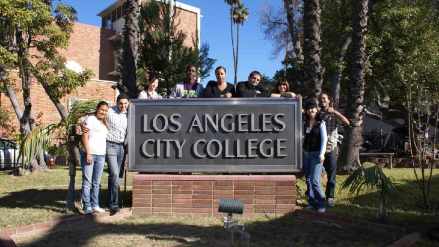 Students stand around a sign displaying the name of their campus, Los Angeles City College, for a photo.