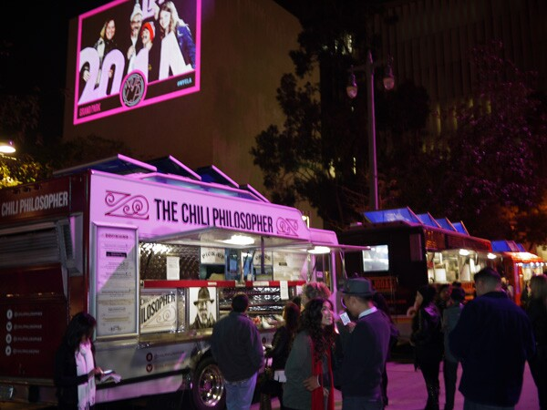 Numerous food trucks are parked to serve revelers, while attendees who take pictures with 2014 props are projected onto a building edifice