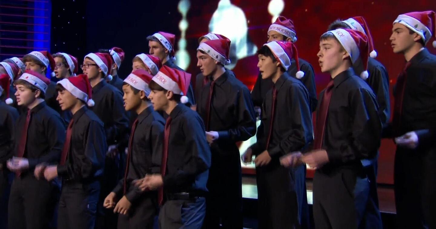 """Choir members wear Santa hats as they sing a song. 