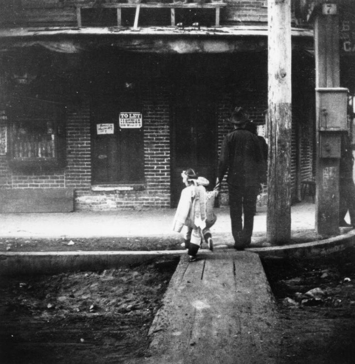 A man assists a child across the street on wooden planks in L.A.'s Old Chinatown, circa 1930s. | Los Angeles Public Library Collection