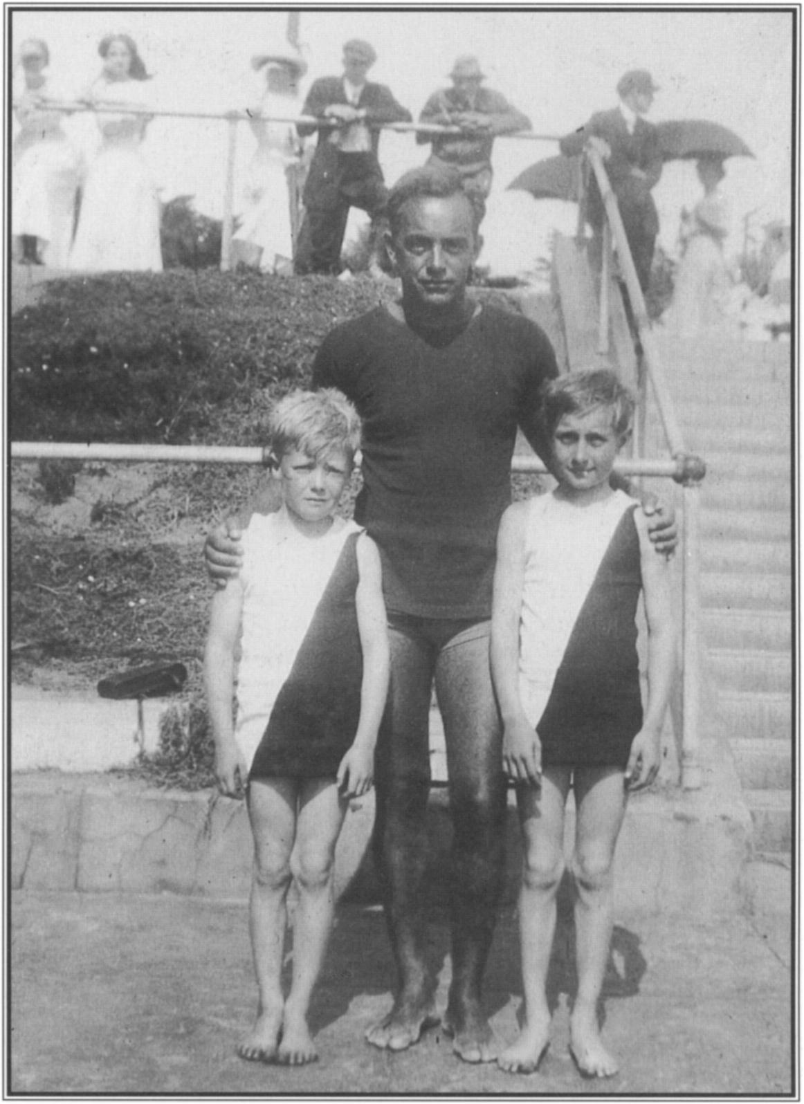 At Redondo Beach in 1910, George Freeth posed with two of his star pupils, brothers Tommy and Jerry Witt. Knock-kneed Tommy, on the left, was to become a div ing champion; Jerry was a nationally ranked swimmer.