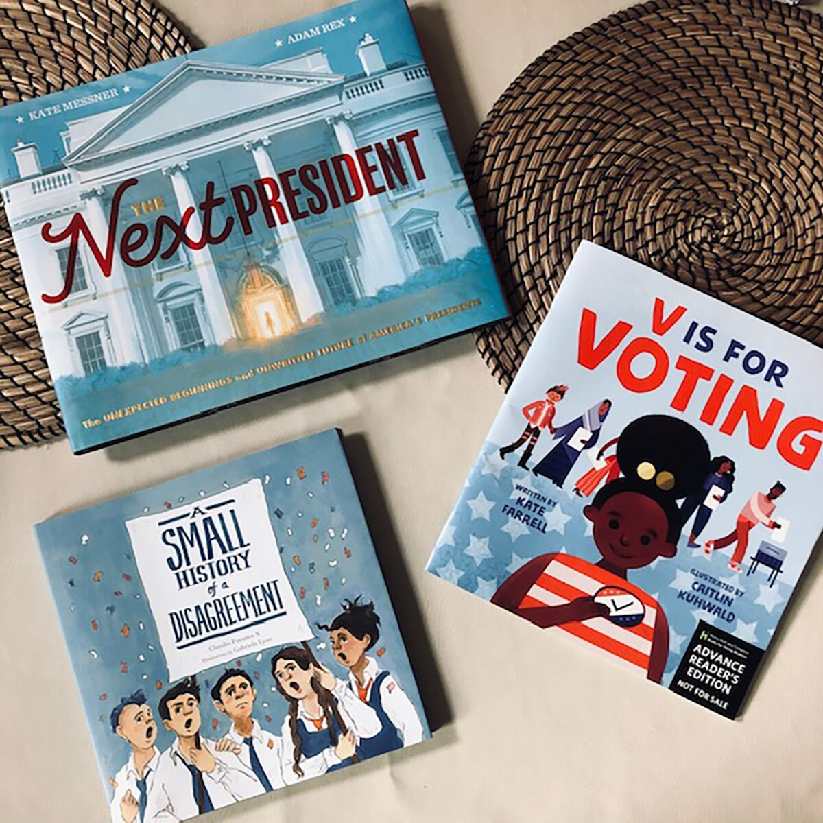 Three blue book covers of kids elections books. One features a cartoon of the White House, another a cartoon of a smiling black girl in a red and white top and the third a cartoon of a group of people talking