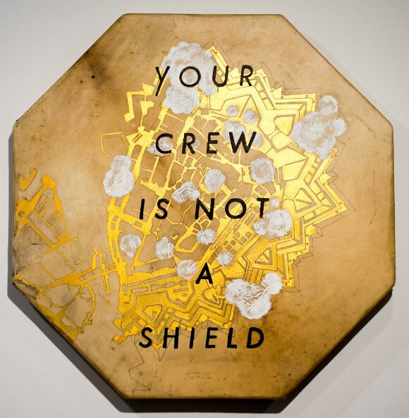 "Frohawk Two Feathers, ""Your Crew Is Not A Shield,"" 2014. Acrylic, ink on elk hide. 33 1/2 × 33 1/2 × 3 in. 