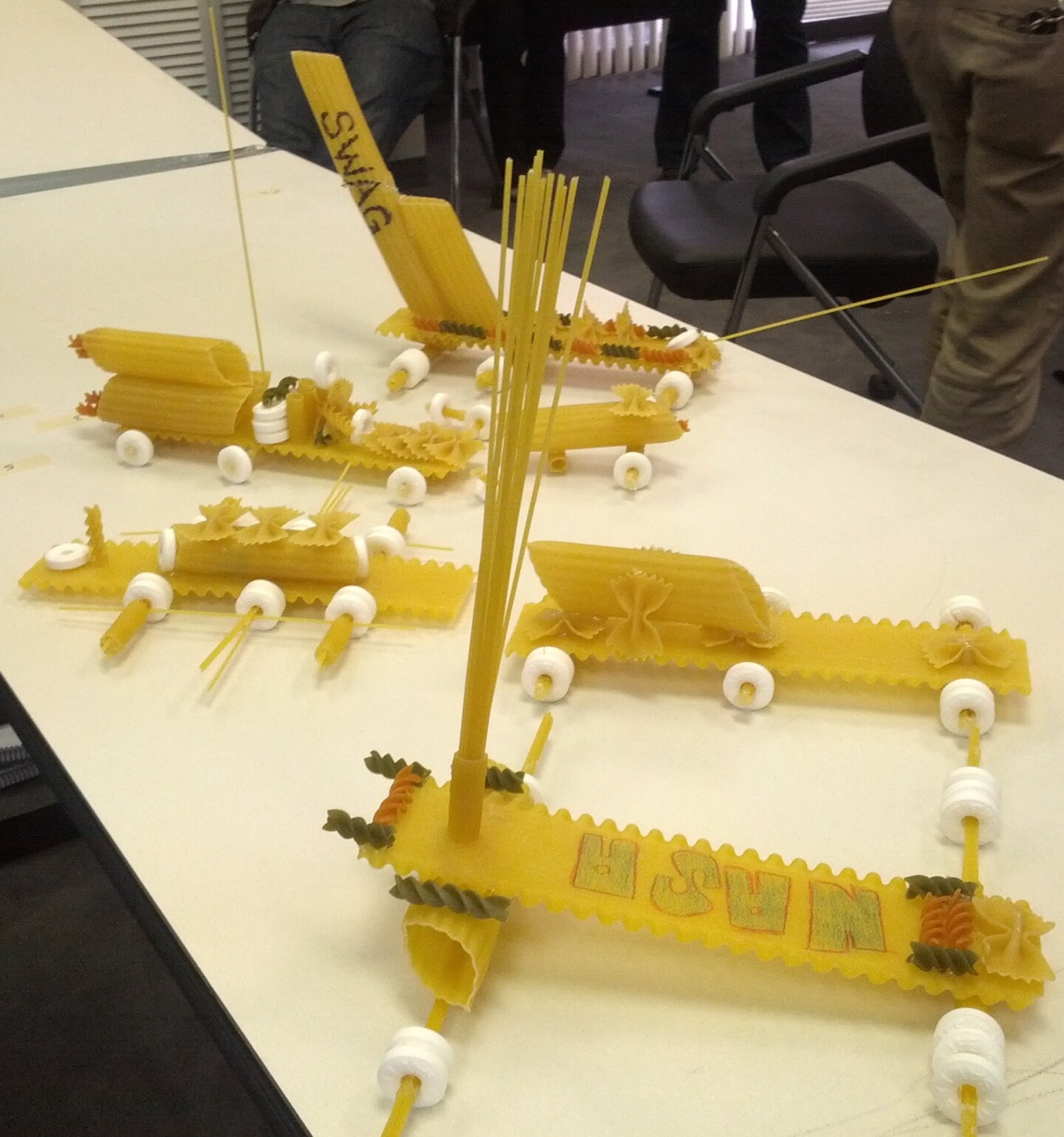 Several rovers made out of dried pasta are laid out on a table.