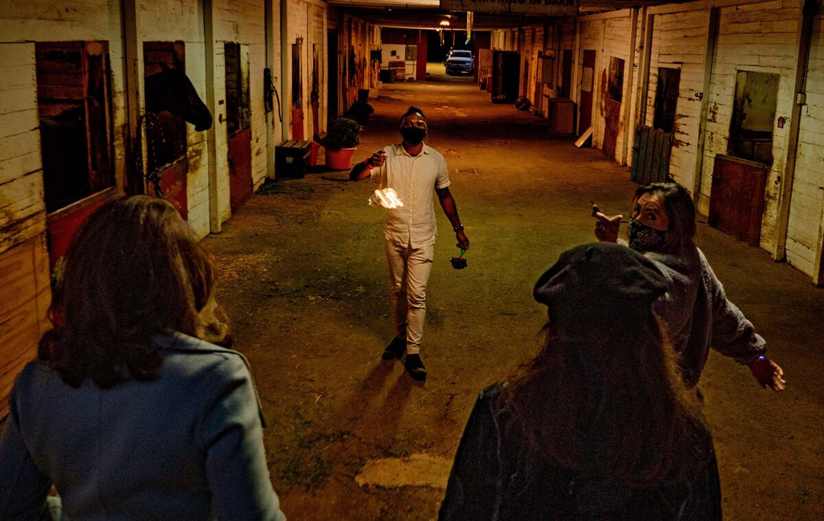 "A performer holds a light in an alley. The performance is part of at ""Firefly Nights,"" an in-person COVID-safe experience that falls within the ""Rio Reveals"" series."