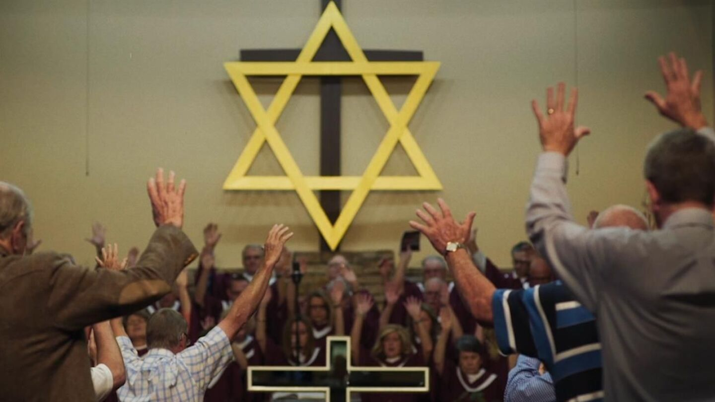 A crowd of people lift their hands during worship toward the Star of David.
