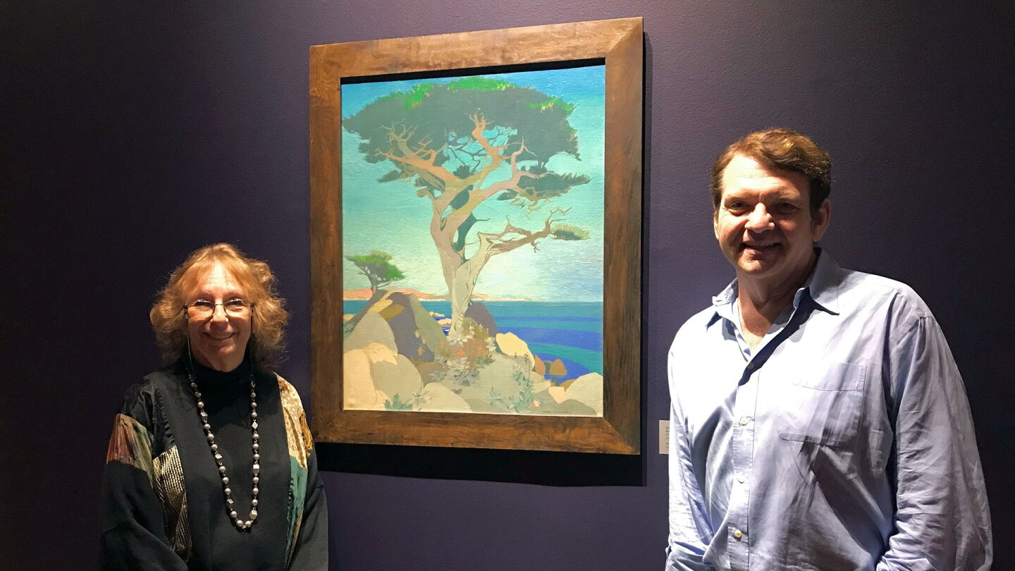 """Exhibition Curator Maurine St. Gaudens and Co-Curator Joseph Morsman with Vivian Stringfield's painting """"Monterey Cypress,"""" circa 1925 exhibited in Something Revealed at the Pasadena Museum of History 