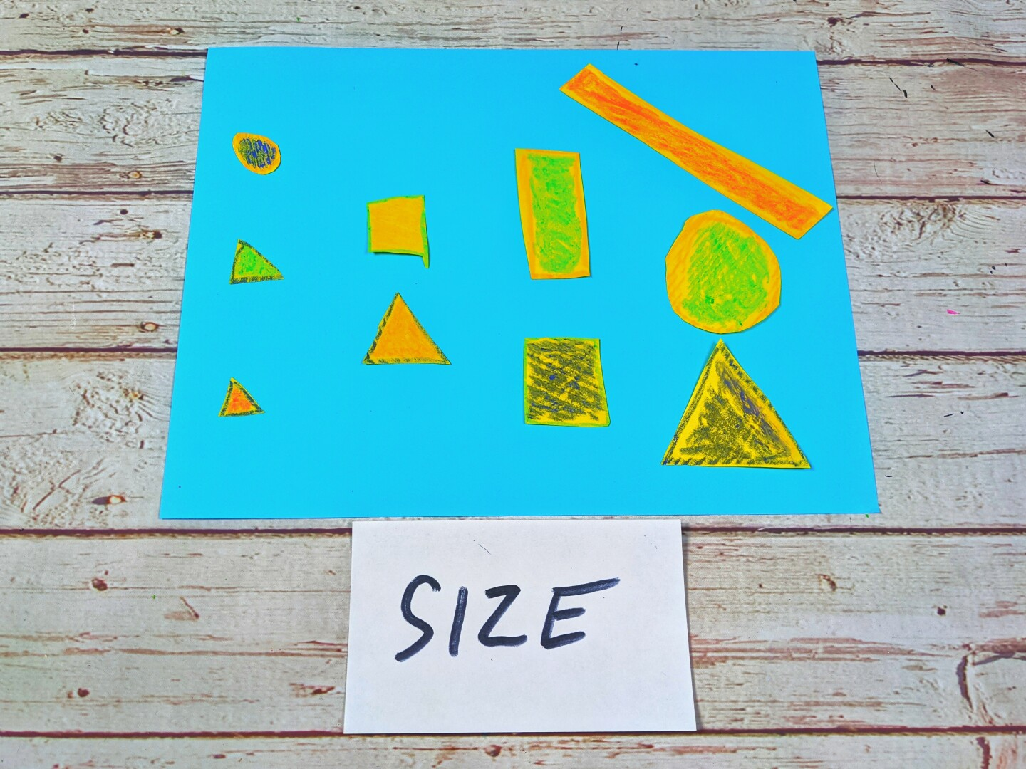 "A blue sheet of paper holds different shapes that are grouped based on their sizes. An index card below reads ""size."""
