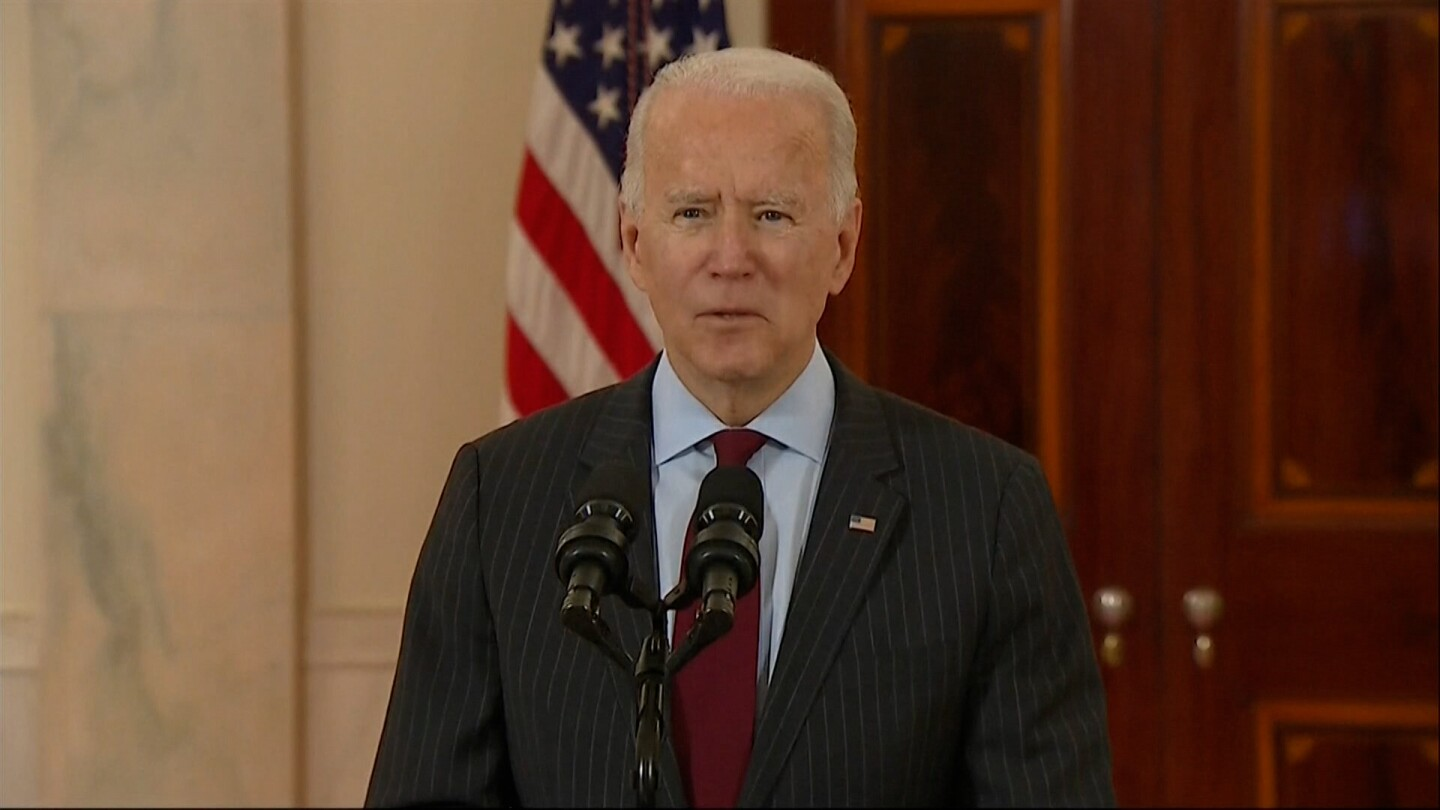 President Joe Biden speaks into microphones at a podium.