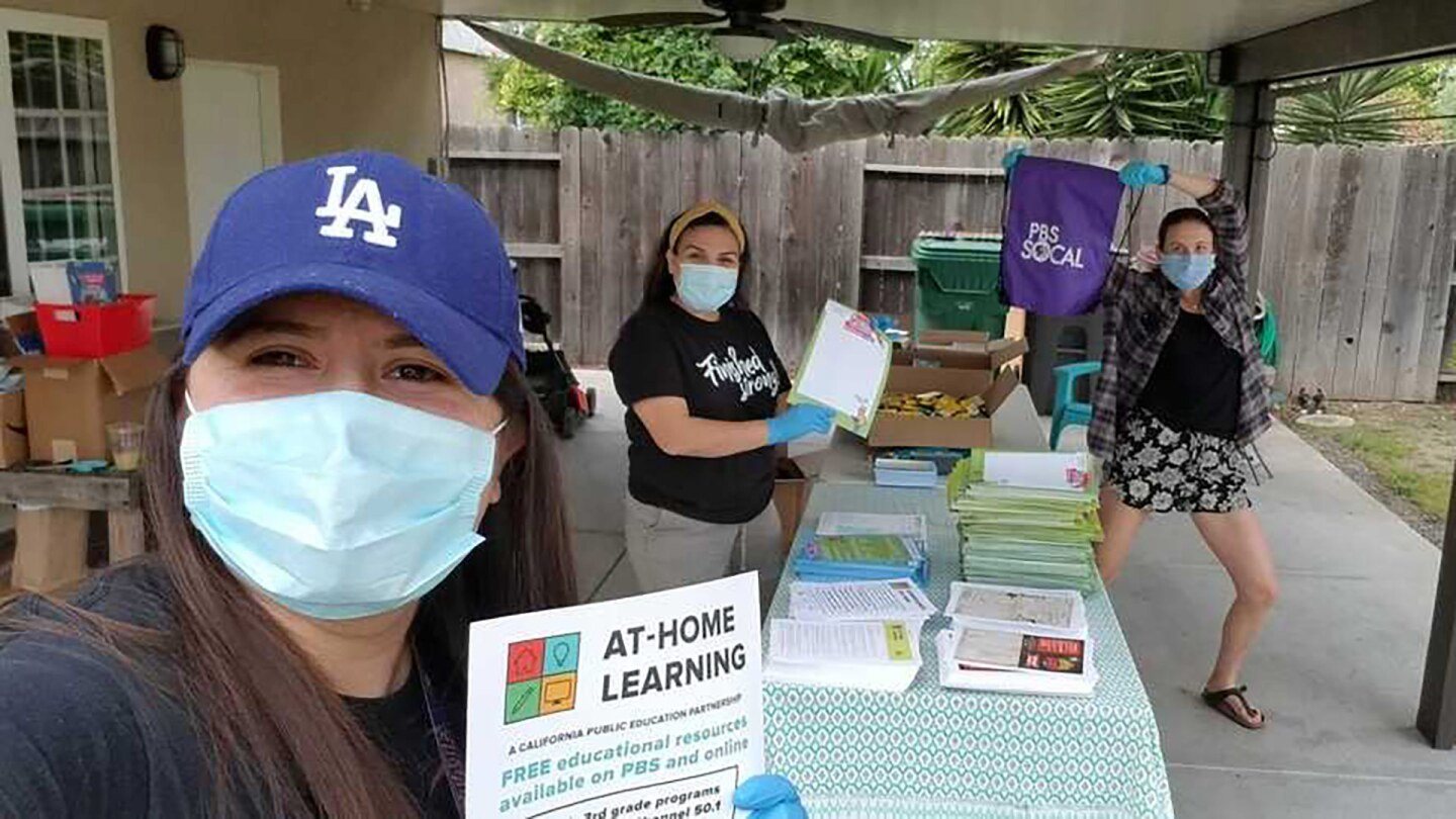 Early learning coordinators, Daniela Valenzuela and Sandra Cruz, along with Suzie Hicks, PBS SoCal's early learning specialist, pack backpacks in Valenzuela's backyard.