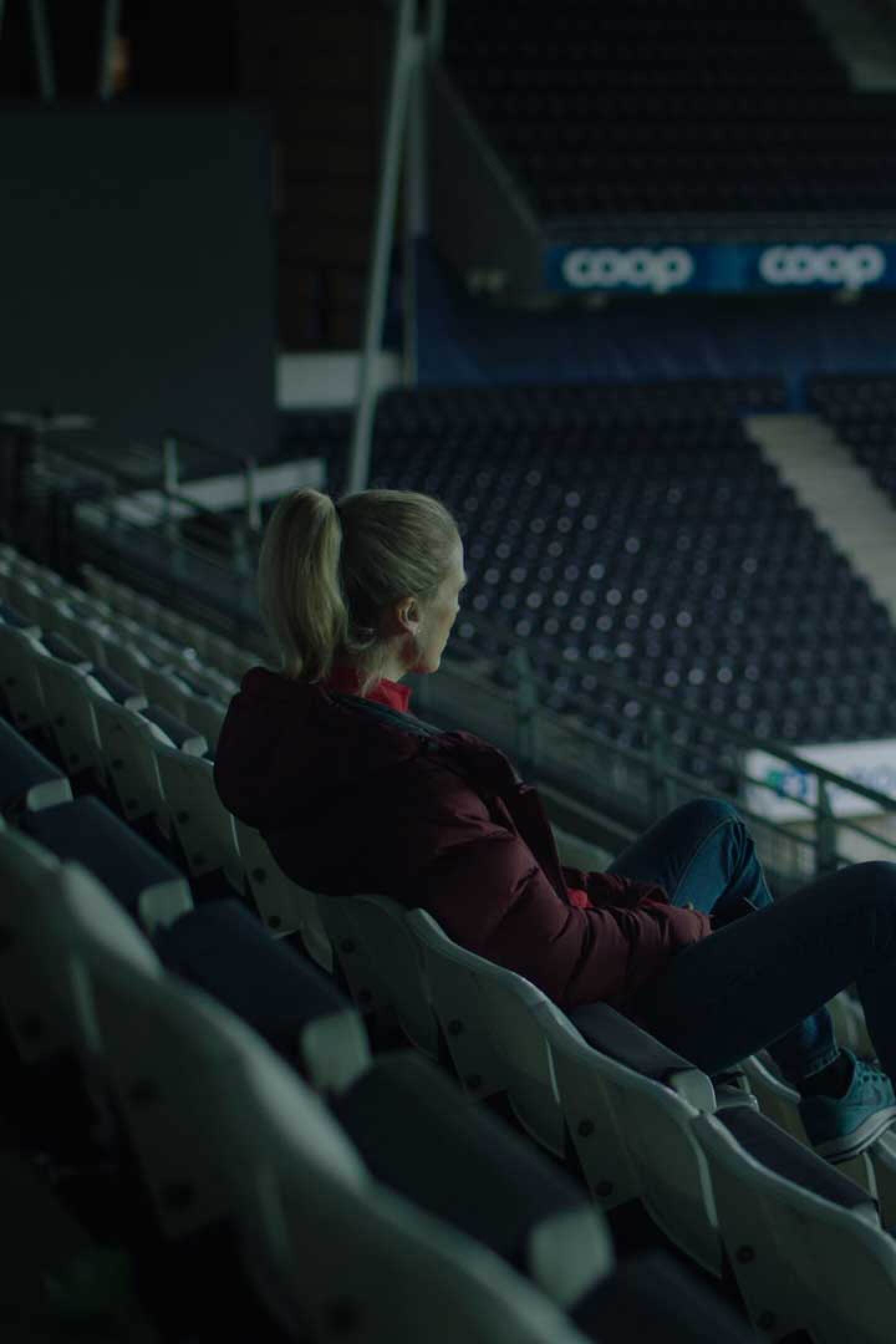 """Helena, played by Ane Dahl Torp, sits in an empty stadium staring out at the field.   """"Home Ground"""""""