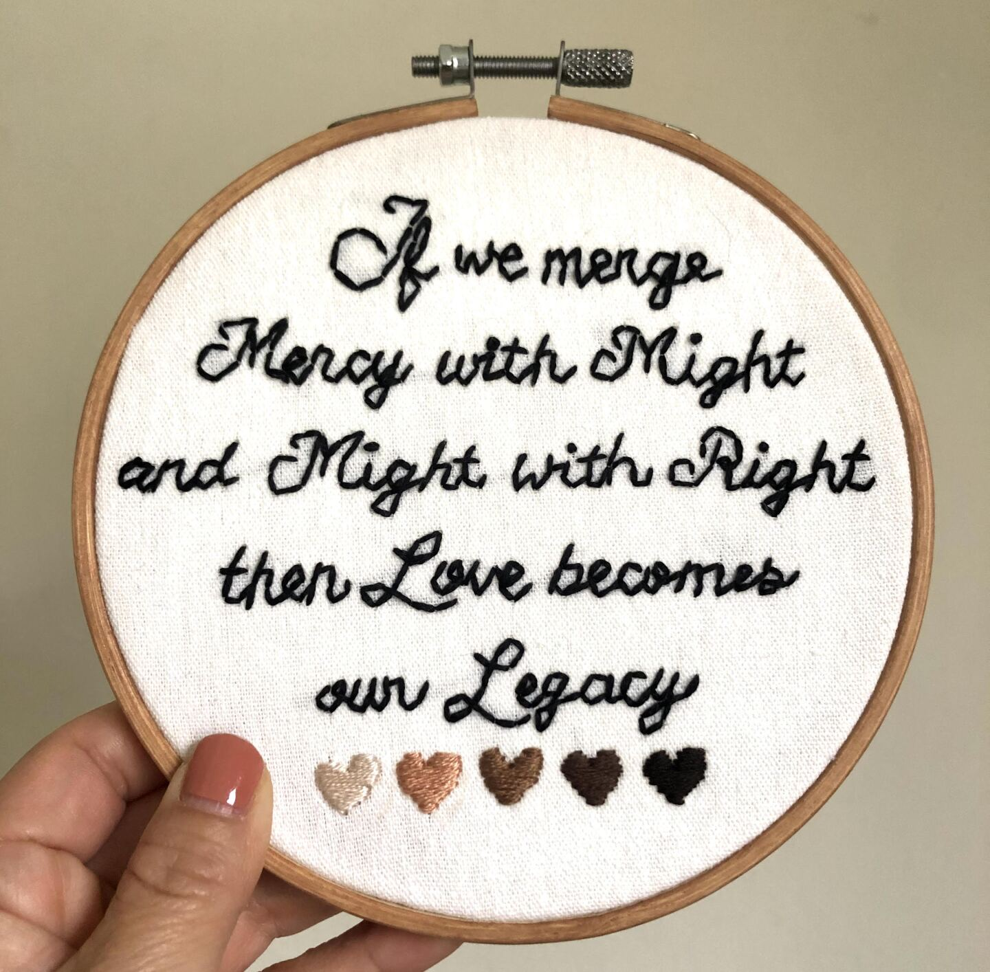"""A hand-held embroidery hoop with white fabric stretched across with the words, """"If we merge mercy with might and might with right, then love becomes our legacy,"""" embroidered in black thread. The words are a quote from Amanda Gorman's inaugural speech. At the bottom of the embroidery hoop design are five flesh-toned embroidered hearts in different shades going from lightest to darkest."""