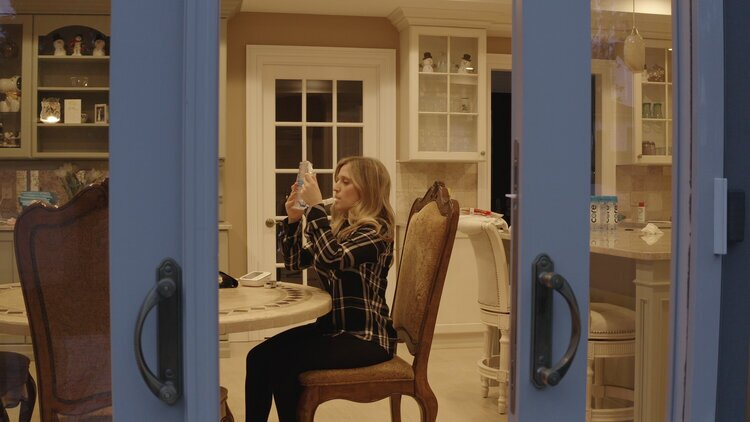 Jennifer is photographed between glass doors, slightly ajar. She is sitting a dining room table and using a respiratory device.