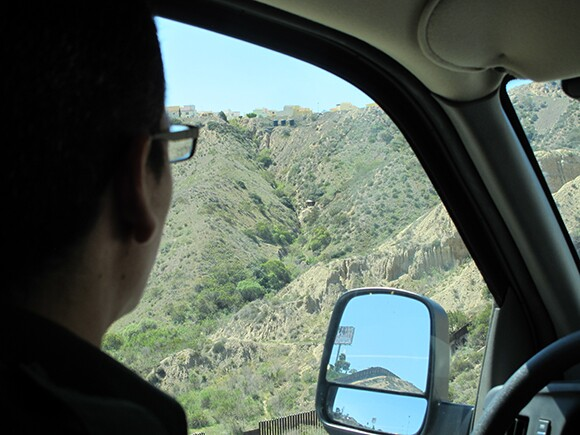 """Our driver, a CBP agent, looks out at Smugglers Gulch where a """"spotter's hut"""" is nestled in the hillside. 