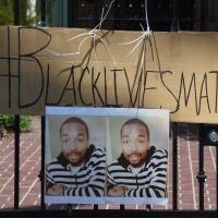 Protest sign showing images of Ezell Ford during Black Lives Matter protest June 2015 | photo Mark Ralston/AFP/Getty Images