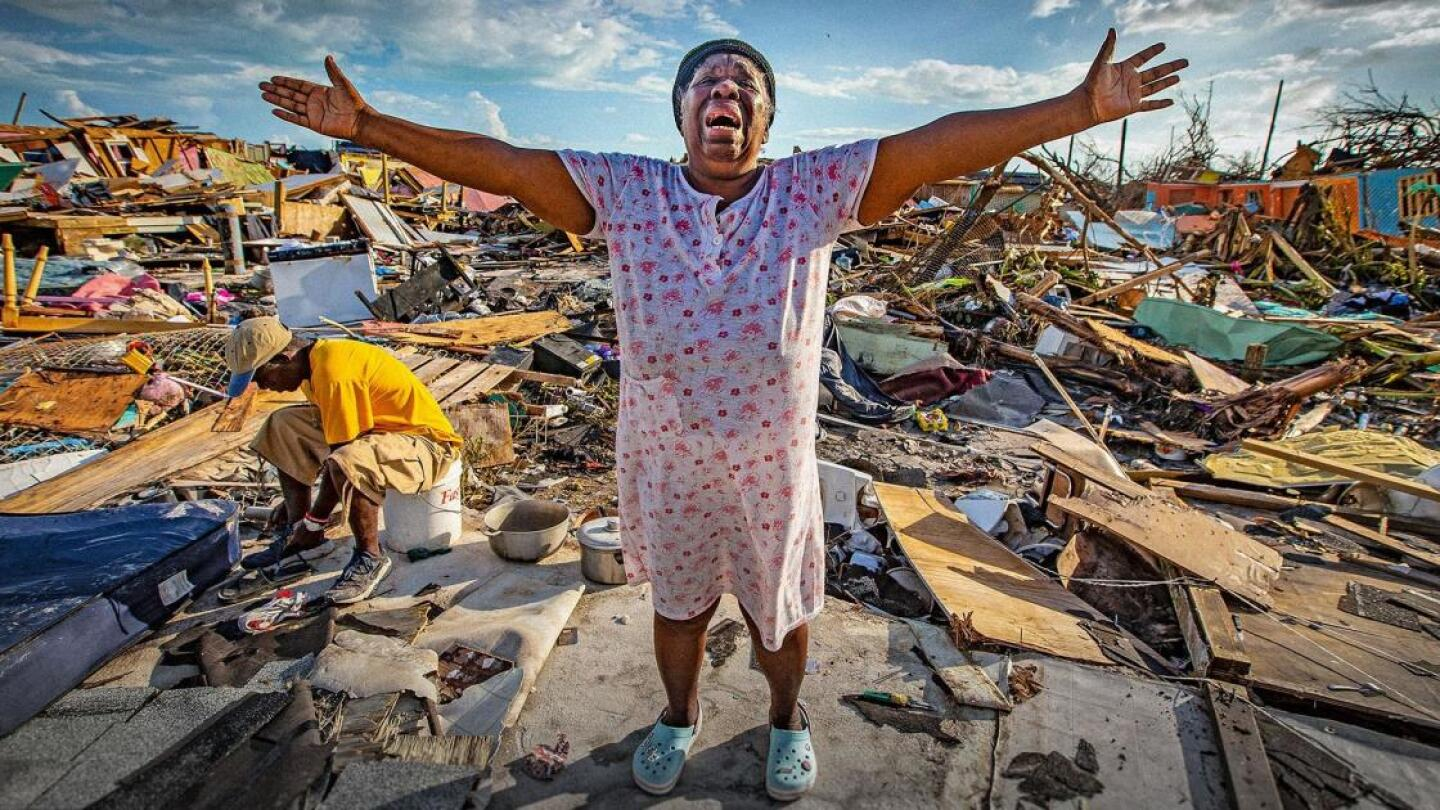 A person stretches out their arms amid wreckage and debris from a hurricane.