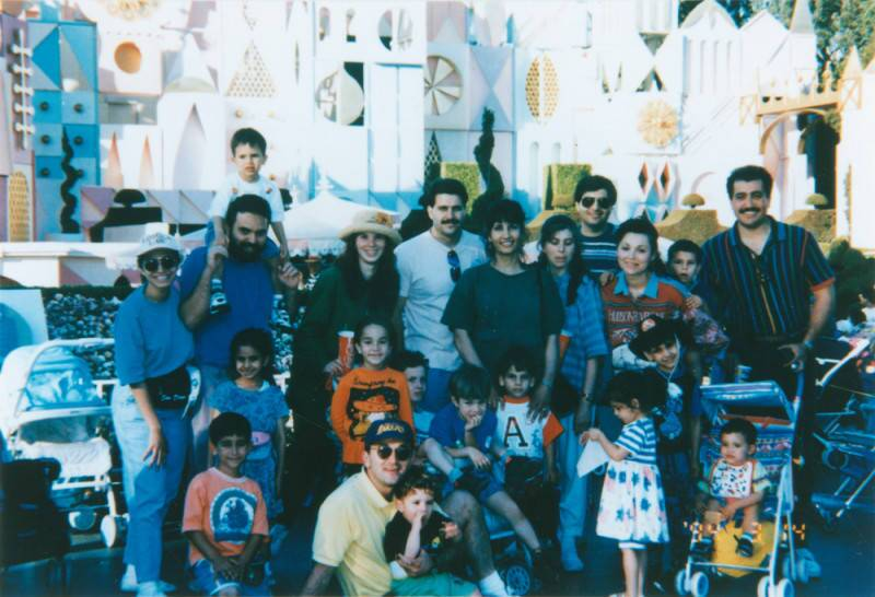 Friends and family pose in front of a ride at Disneyland, 1994