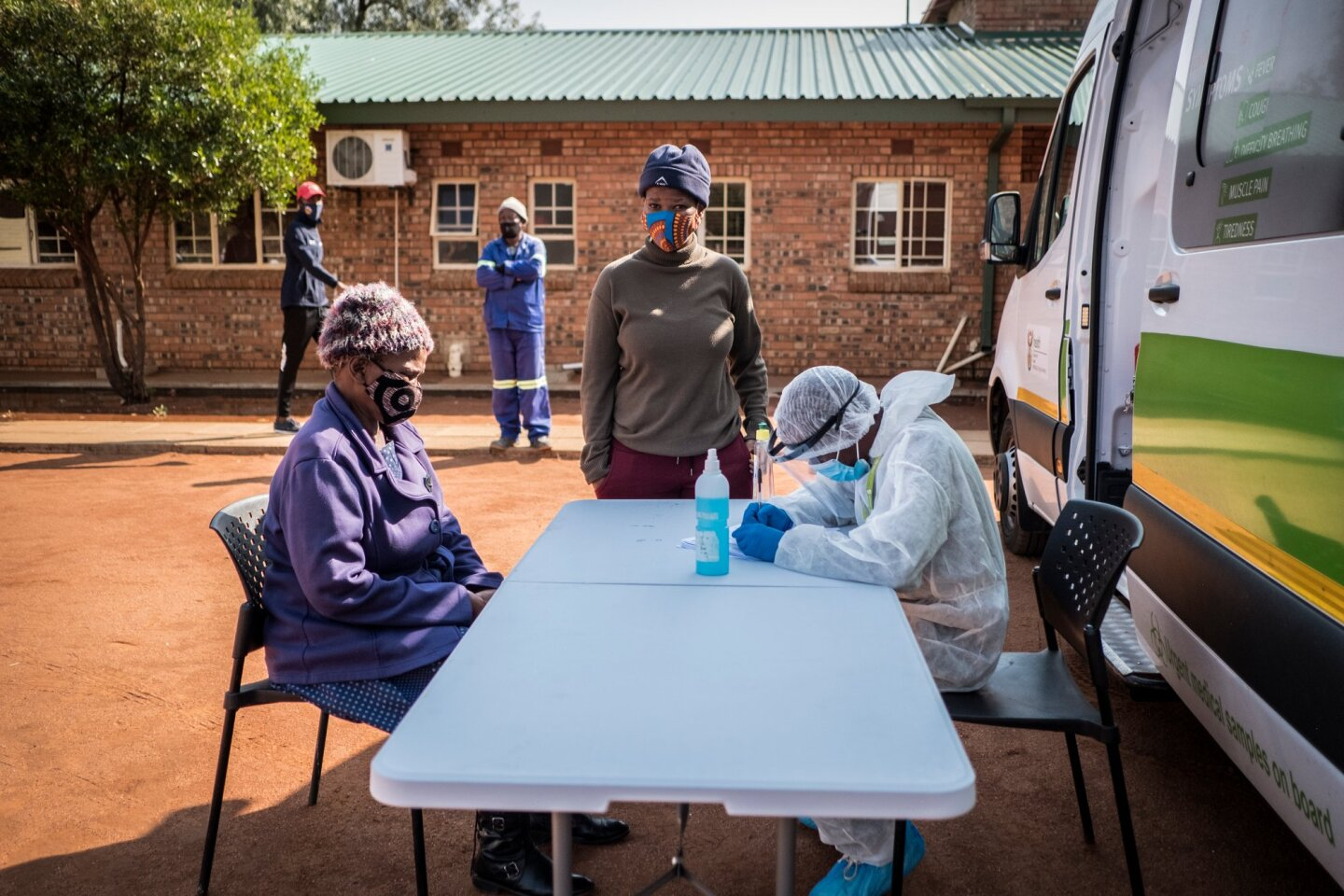 A nurse wearing PPE assess a masked person sitting in front as another masked person looks on. | Thomson Reuters Foundation