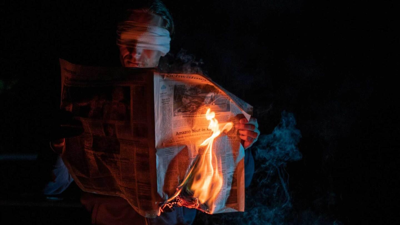A blindfolded man reading a burning newspaper   Max Muselmann / Unsplash