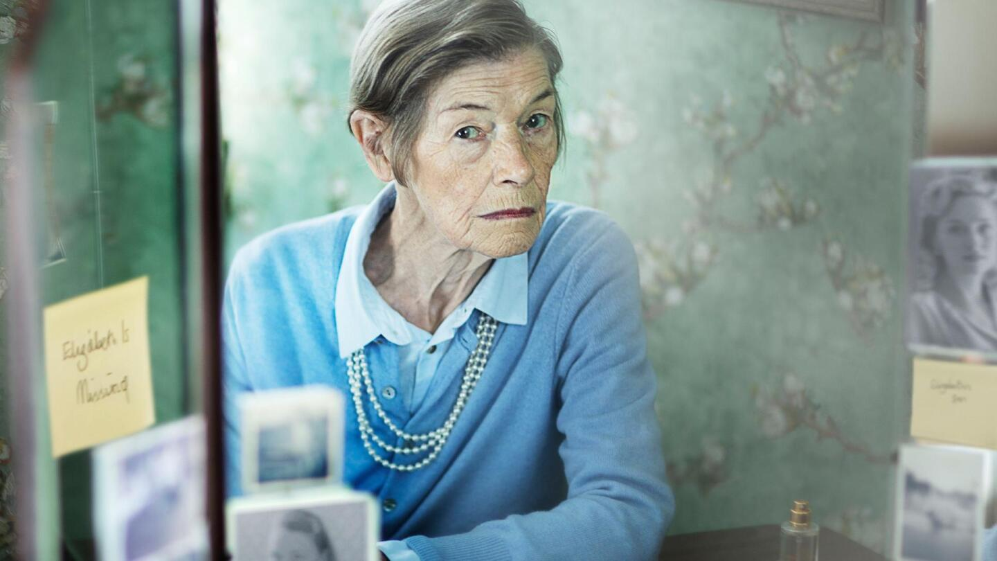 A elderly woman with a skeptical expression sits by a table.