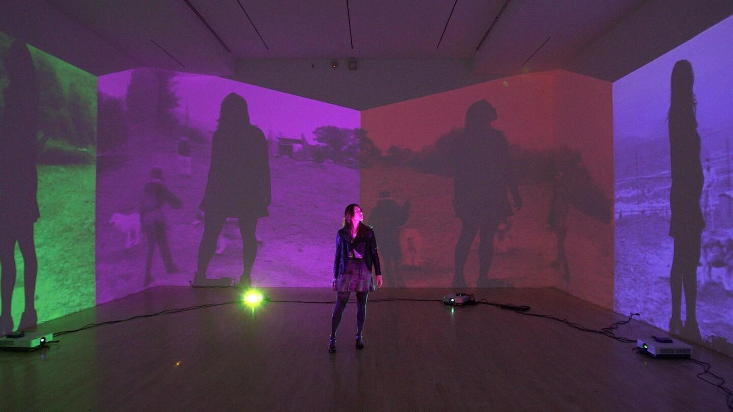 """A woman standing in a room with her silhouette projected on four different screens. 