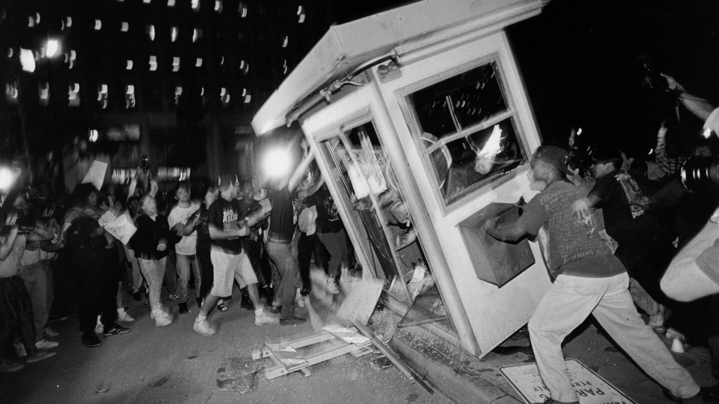 Rioters overturn a parking attendant booth at the LAPD Parker Center in downtown Los Angeles during the 1992 riots. | Ted Soqui/Corbis via Getty Images