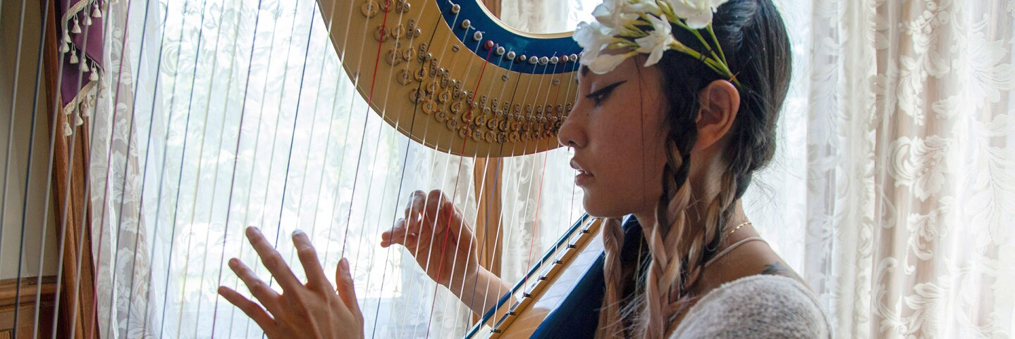 Low Leaf plays her harp inside the Perry House at Heritage Square Museum. | Azul Amaral
