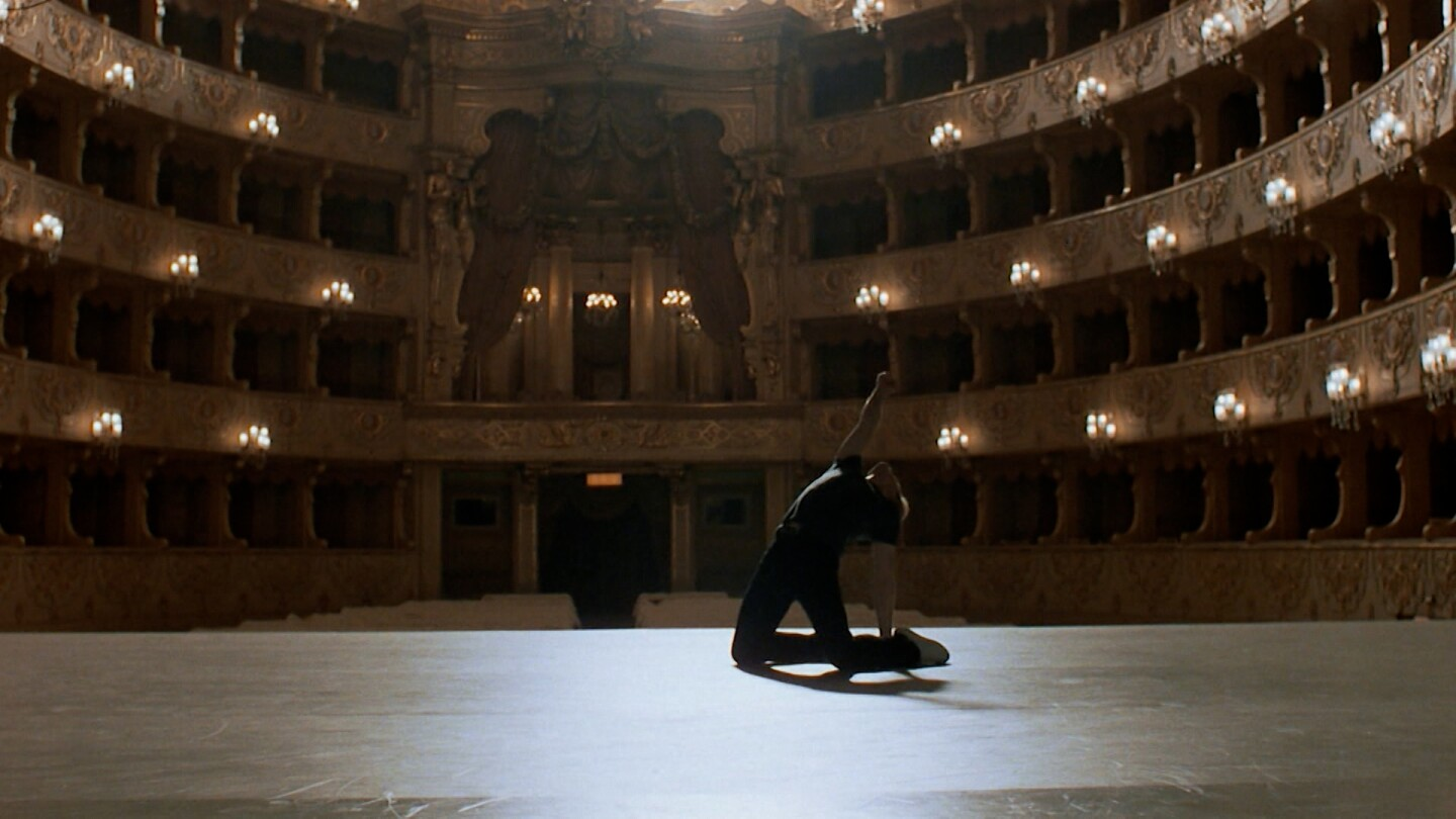 "A dancer performs passionately in an empty performance hall. | ""White Nights"""