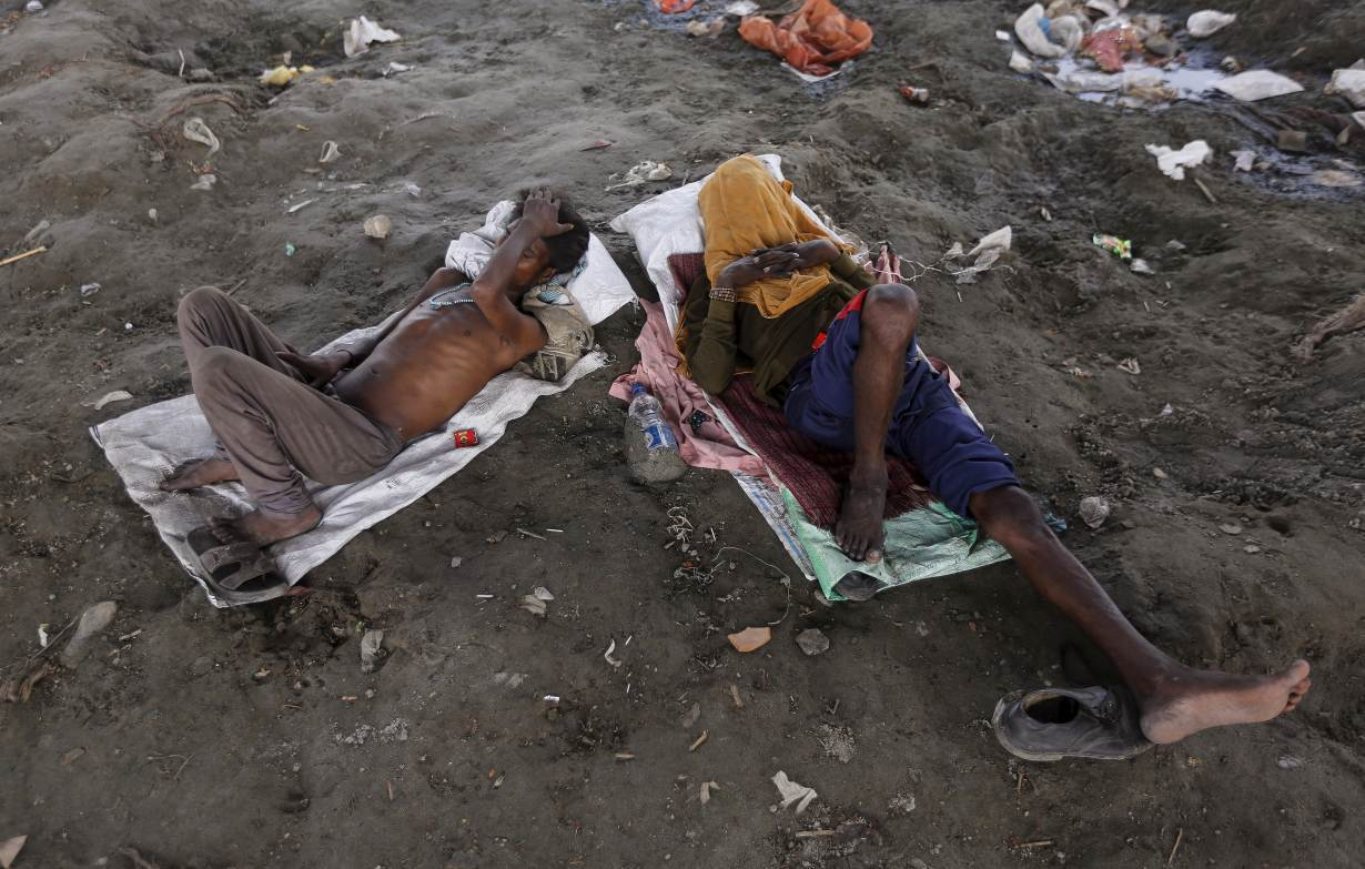 ARCHIVE PHOTO: People sleep on the Yamuna river bed under a railway bridge during a hot summer day in the old quarter of Delhi, India, May 31, 2015. | REUTERS/Adnan Abidi