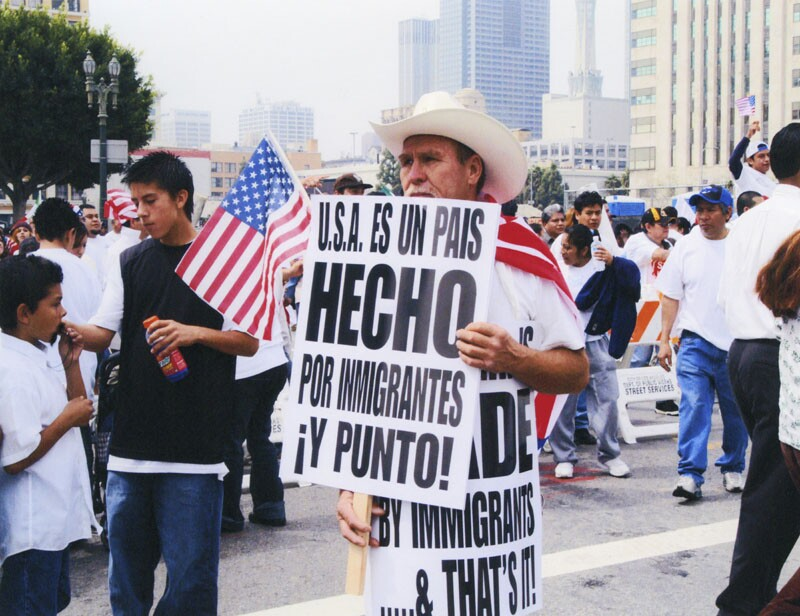 """Day Without an Immigrant protester holds signs in English & Spanish that read: """"U.S.A. is MADE by immigrants... & that's it!"""" Photo is courtesy of the LAPL."""