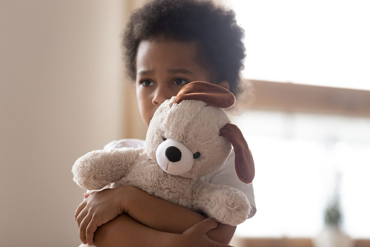 A sad-looking little boy hugs a stuffed dog tightly. iStock