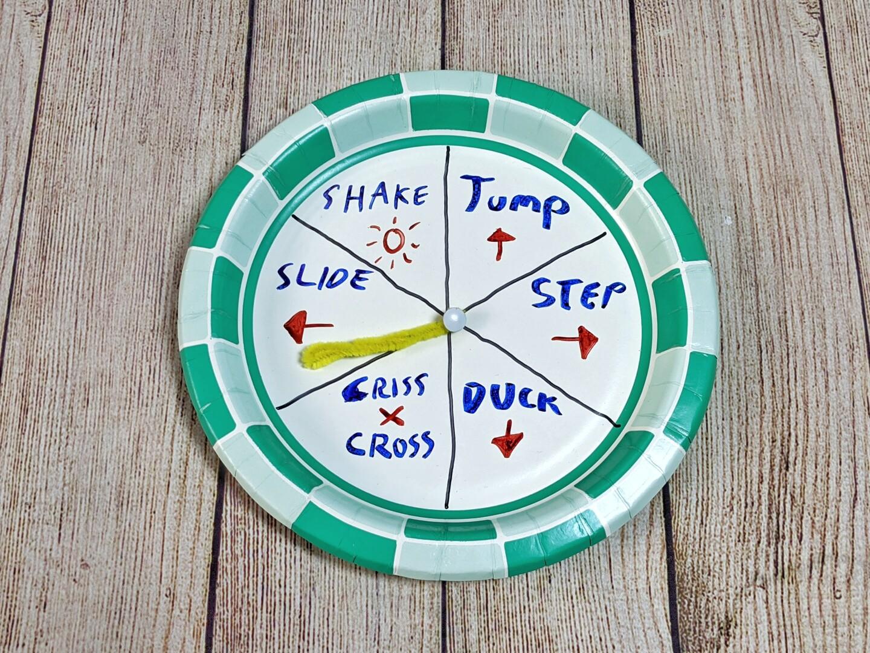 Una ruleta hecha de un plato de papel está dividida y marcada con instrucciones como de un paso a la derecha, brinque y agáchese.
