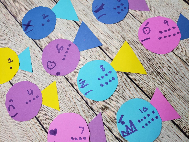 Coloridos recortes en forma de pececitos, cada uno etiquetado con un número del uno al 10, están acomodados sobre una mesa de madera.