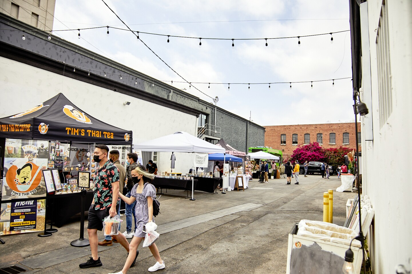 """Masked and arm in arm, two attendees walk through the booths and tents at the FilLed Market in Downtown L.A. A nearby tent reads, """"Tim's Thai Tea."""" The attendees are holding miscellaneous plastic bags and a bag with drinks."""