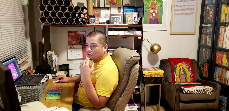 Julio Salgado works on a laptop at a desk.