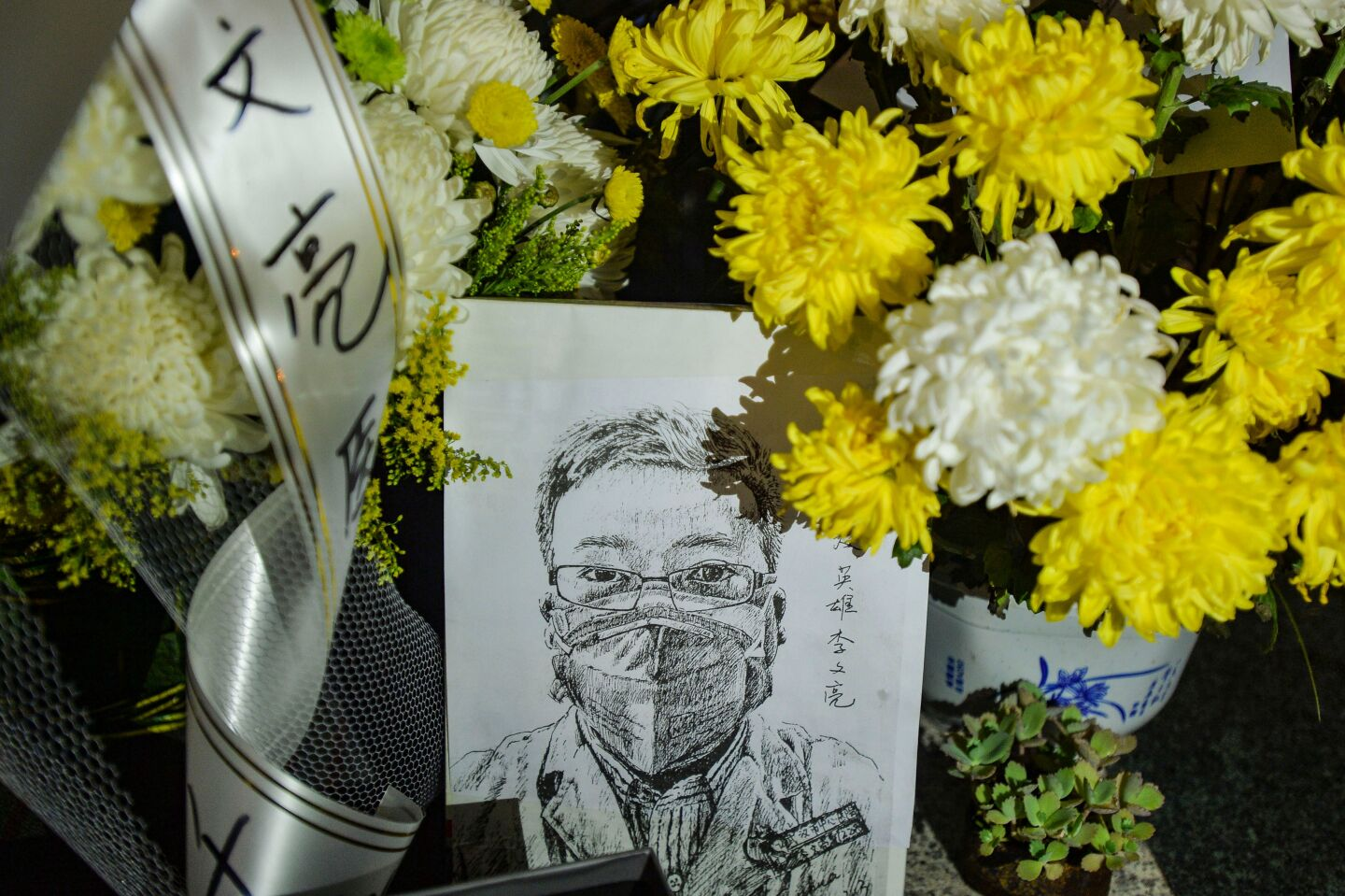 A memorial with flower bouquets honoring the late ophthalmologist Li Wenliang, who died after becoming infected with SARS-CoV-2, at the Houhu Branch of Wuhan Central Hospital in Wuhan in China's central Hubei province.