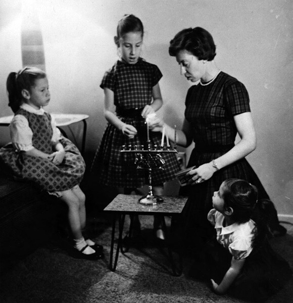 Lee lights the third candle of  Hanukkah  with her three daughters, Susan, Karen and Diana. | Courtesy of the Los Angeles Public Library