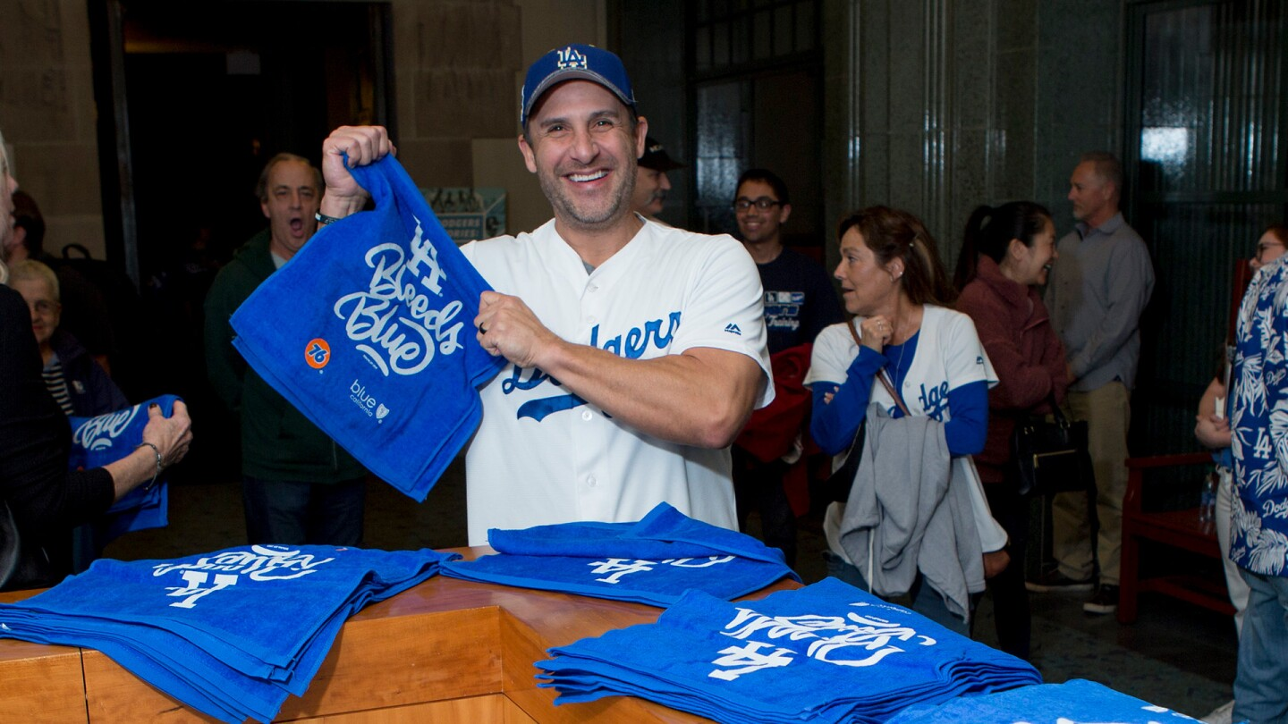 Dodgers fan, Shon Flores, enjoys special event giveaways following the screening at the Los Angeles Central Library on November 23, 2019.