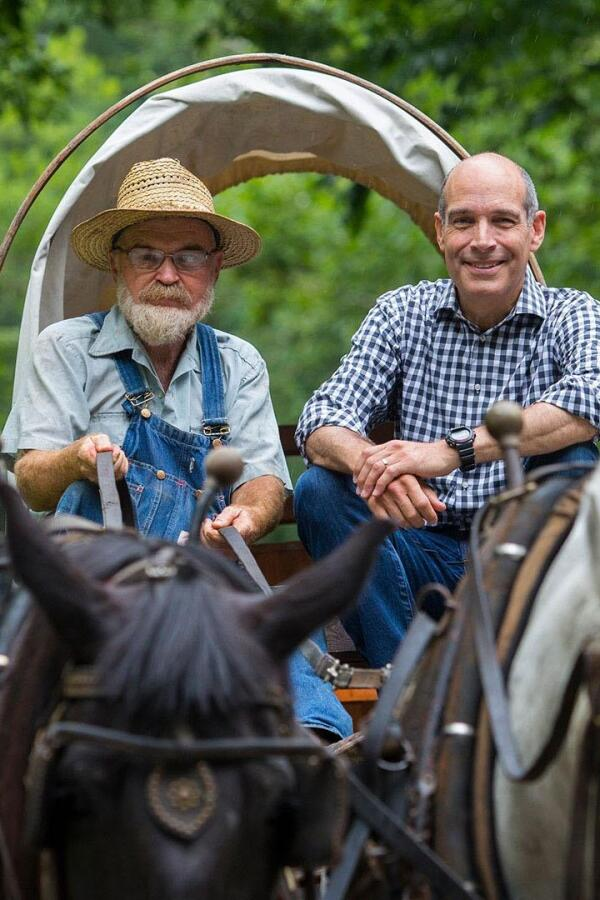 """10 That Changed America"" host Geoffrey Baer sits in a horse carriage with another man holding the reins. 