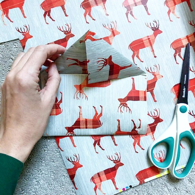 A piece of wrapping paper with red deer on it folded up into an envelope shape with scissors next to it.