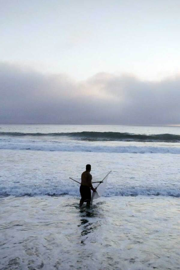 A member of Tolowa Dee-ni' Nation casts his net the beach. | Still from Tending Nature
