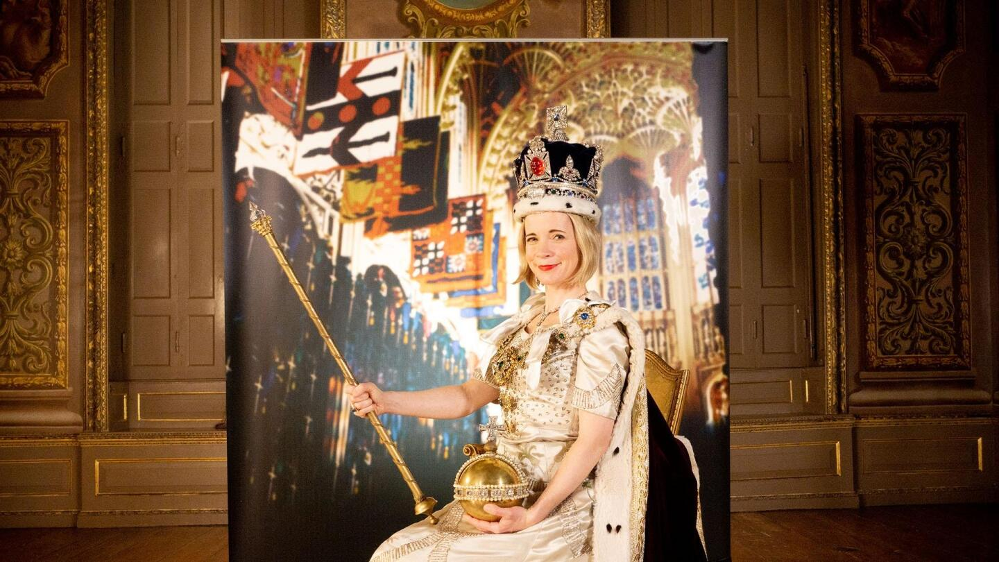 """Lucy Worsley poses with a crown, orb and sceptre. 