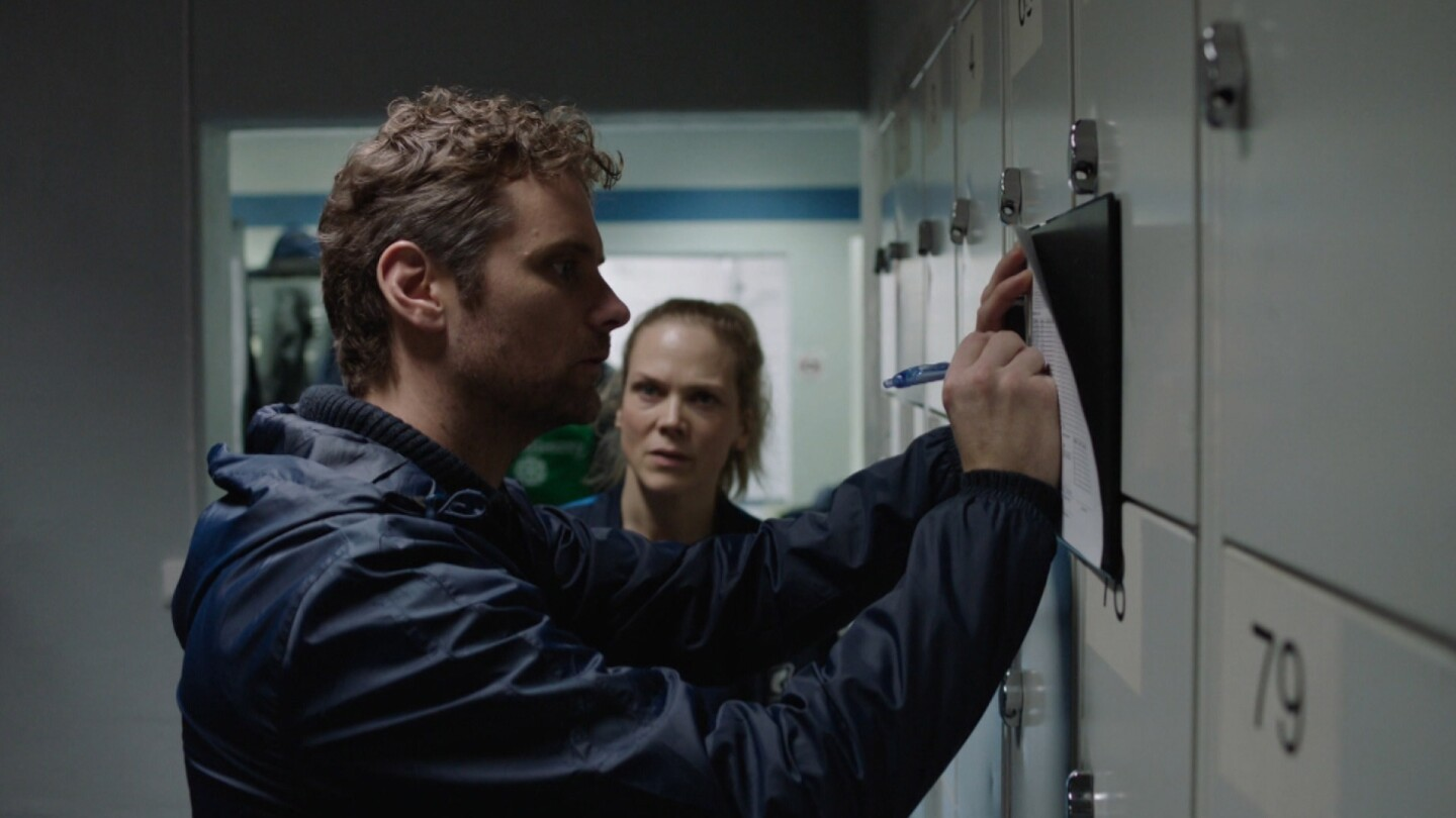 "Helena faces Espen as he writes on a piece of paper against a locker door. | ""Home Ground: Reserve Team"""