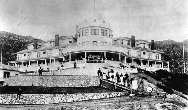 View of some of the hotel guests standing on the veranda and stairways at the front of Echo Mountain House. | Courtesy of the Los Angeles Public Library