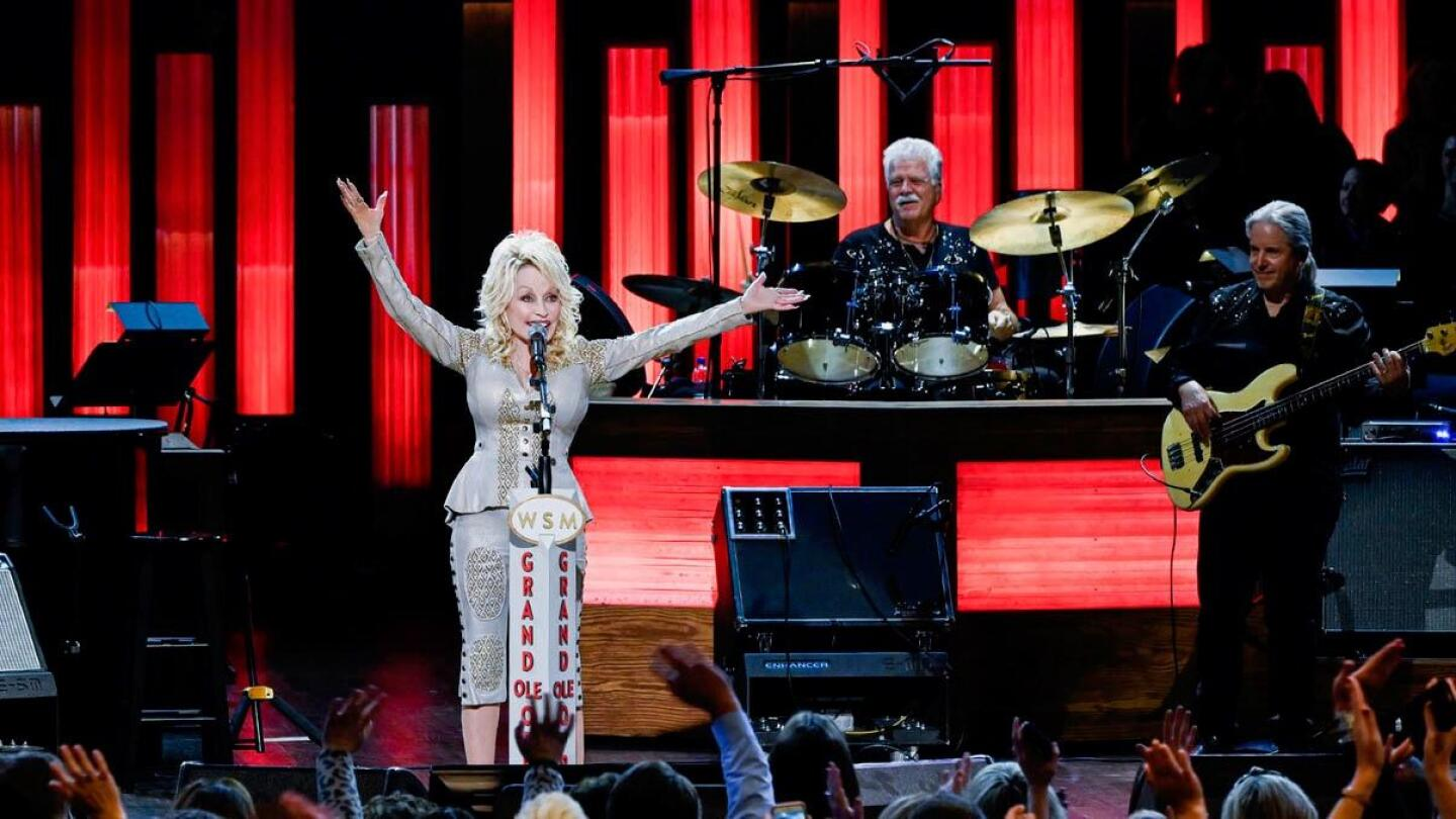 """Dolly Parton outstretches her arms during a performance on stage. 