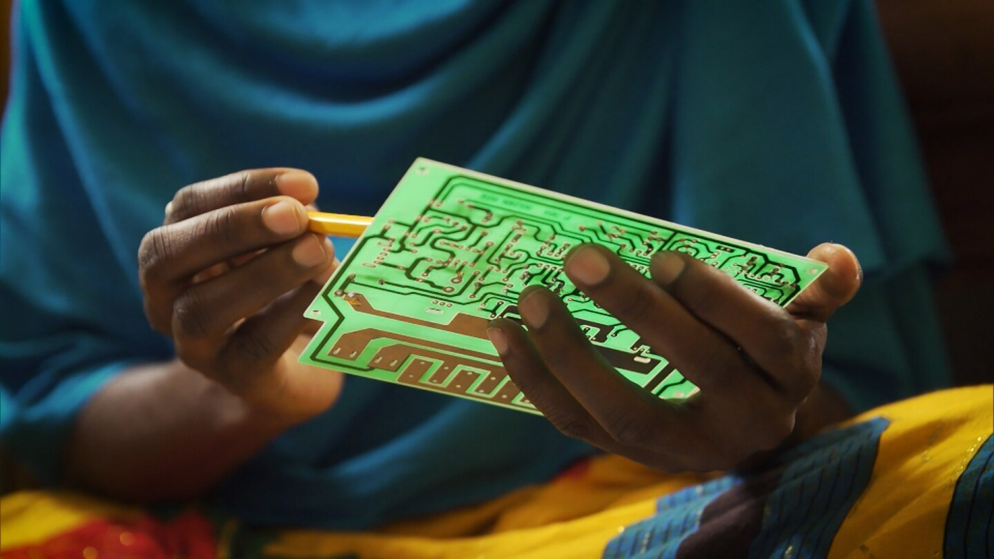 "A woman holds an electronic circuit board. | Still from ""Earth Focus"" episode ""Lighting a Path"""