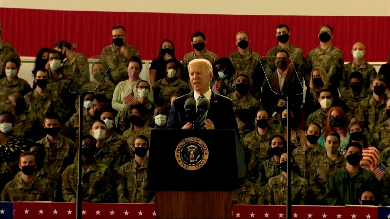 President Biden makes a speech with uniformed troops standing behind him.