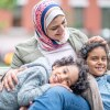 A smiling woman wearing a hijab sits with two smiling children on a bench. | stock